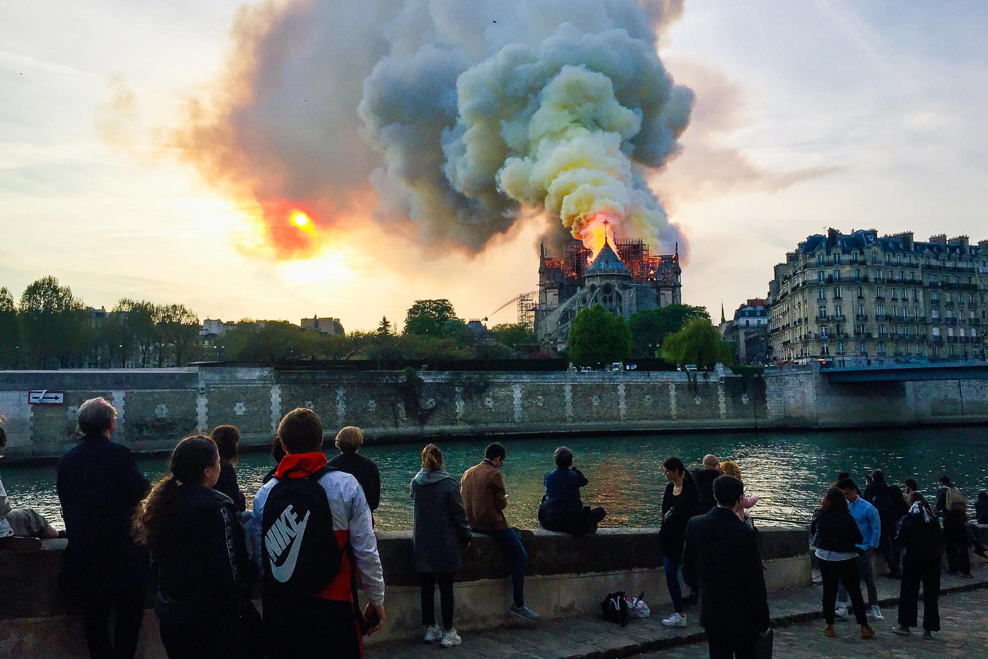 A járókelők lesújtva nézik a lángokat és a hatalmas füstfelhőket