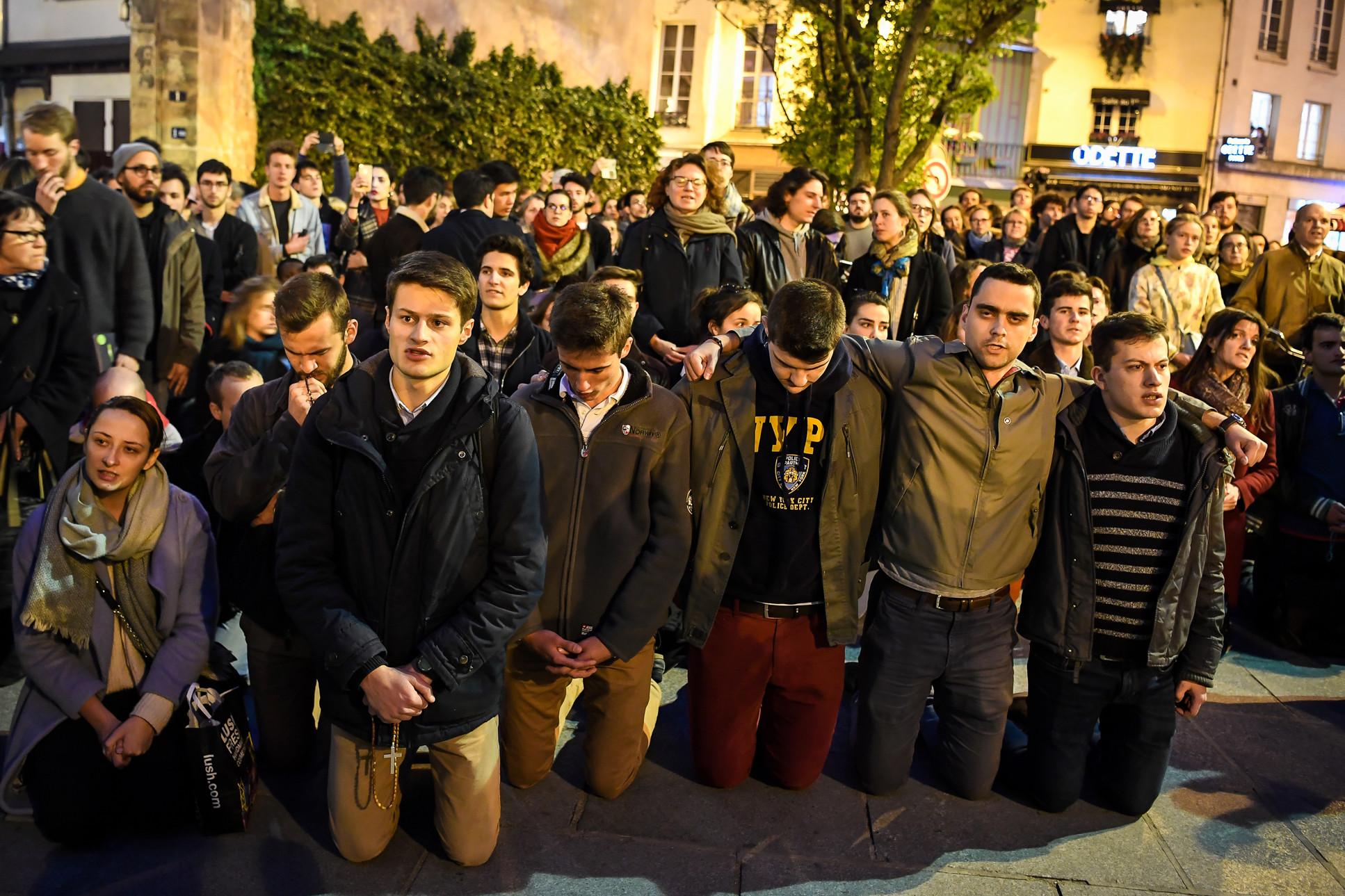 Az emberek a járdán térdelve imádkoznak a katedrális közelében