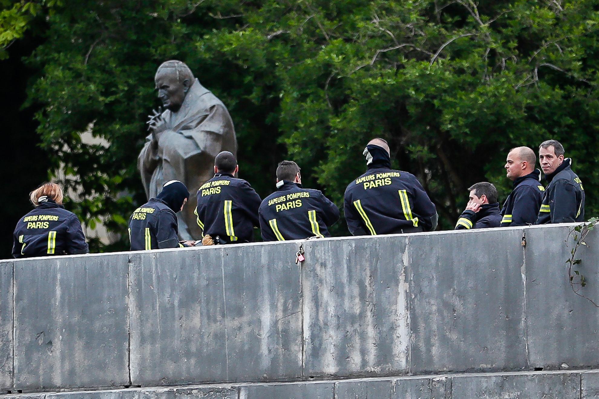 Tűzoltók a II. János Pál pápa-szobornál a tűz másnapján