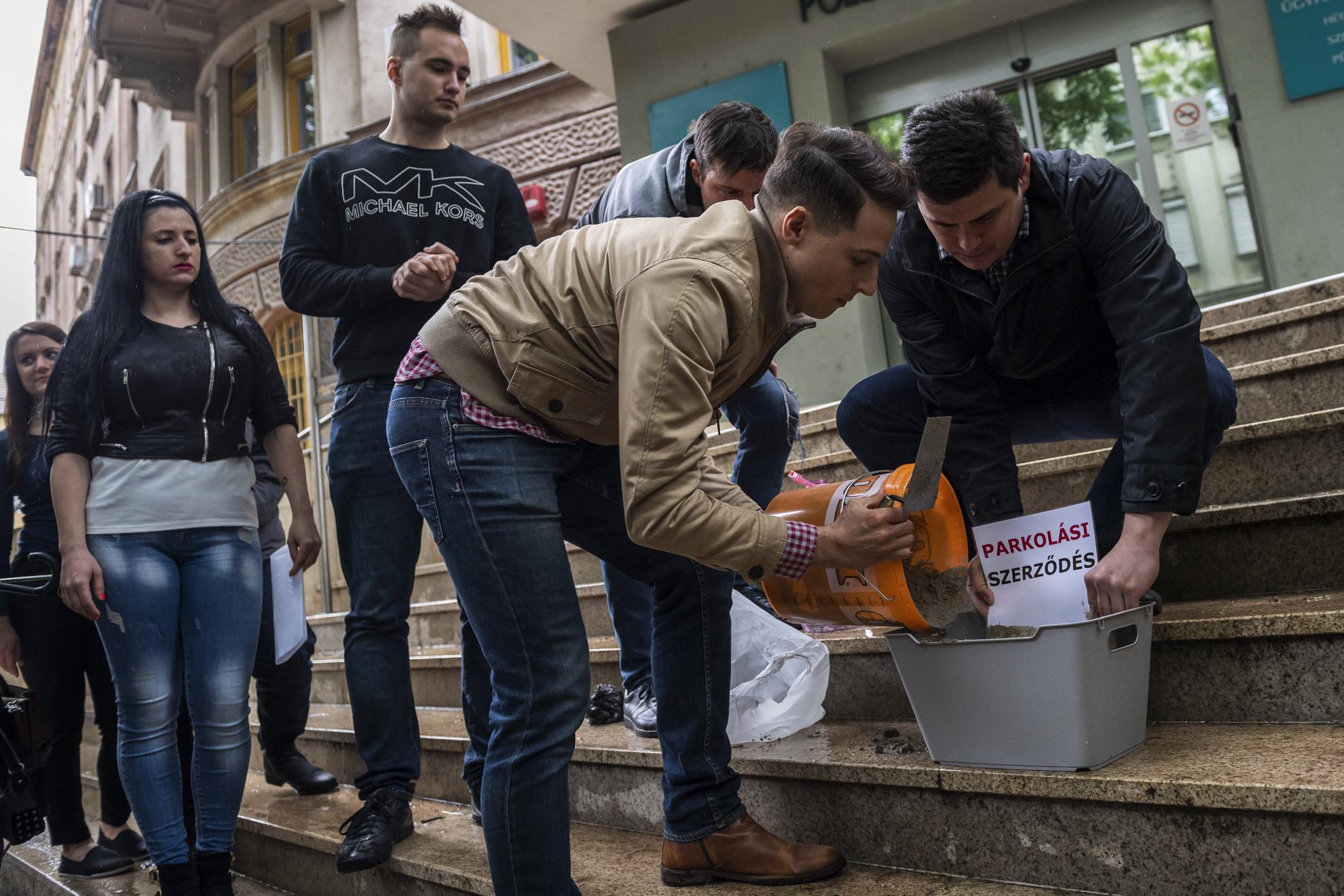 Borbély Ádám, a Fidelitas budapesti elnöke (j2) és a politikai ifjúsági szervezet szimbolikusan bebetonozza a zuglói parkolási szerződést a zuglói önkormányzat épülete előtt