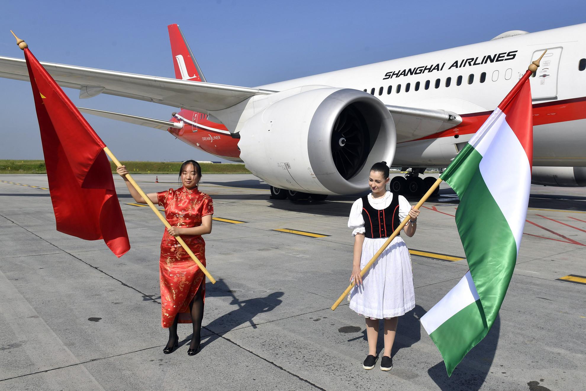 Magyar és kínai zászlóval köszöntik a Shanghai Airlines repülőgépét érkezése napján a Budapest Liszt Ferenc Nemzetközi Repülőtéren