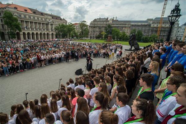 Szarka Tamás Kossuth-díjas énekes, zenész, zeneszerző (elöl, k) és diák éneklik a Kézfogás című dalt, a magyar összetartozás himnuszát a nemzeti összetartozás napján rendezett ünnepségen a Parlament előtt