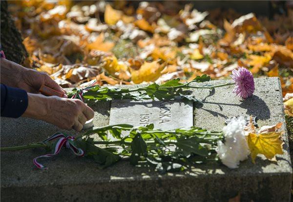 Egy megemlékező mécsest gyújt egy síremléknél a Rákoskeresztúri új köztemető 301-es parcellájában