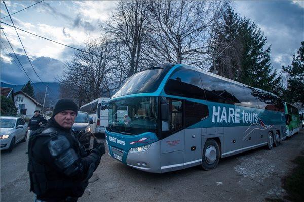Készenléti rendőr egy busz előtt az északnyugat-boszniai Bihácshoz közeli vucjaki migránstábor mellett 2019. december 10-én