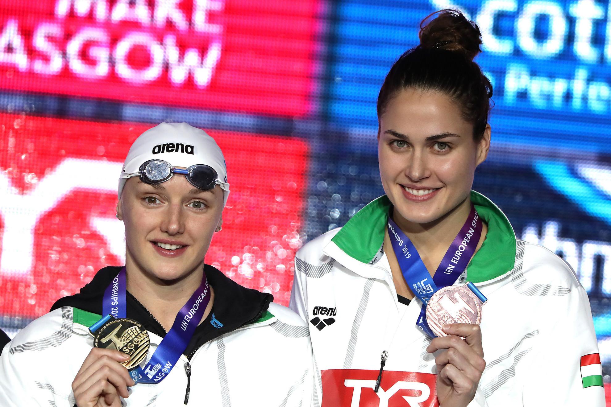 Az aranyérmes Hosszú Katinka (b) és a bronzérmes Jakabos Zsuzsanna a 200 méteres pillangóúszás eredményhirdetésén a glasgow-i rövidpályás úszó Európa-bajnokságon 2019. december 6-án