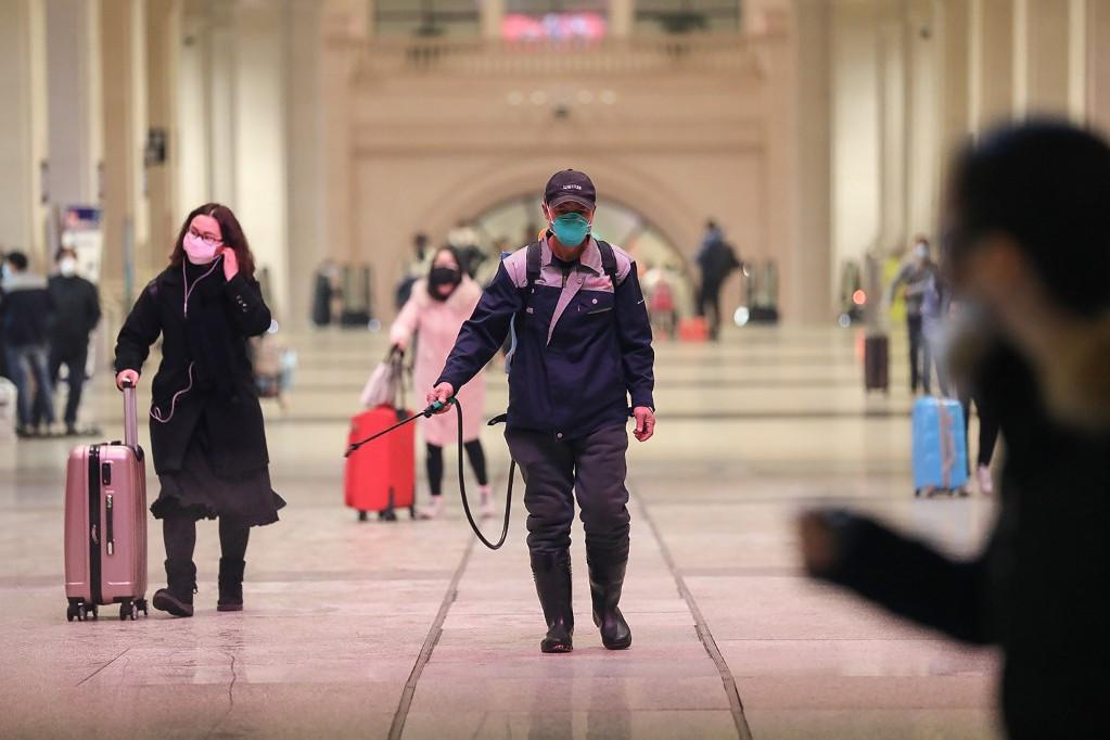 Egy dolgozó fertőtlenítést végez a vuhani pályaudvaron