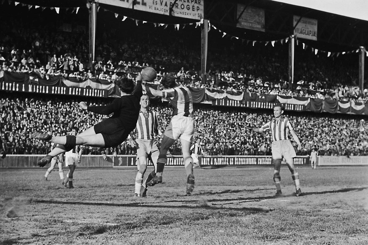 Fradi–Újpest rangadó (4:3) az Üllői úton, 1949-ben. Két évvel később a vetődő Henni Géza kényszerből már a lila-fehéreket szolgálta mint a Bp. Dózsa kapusa, Csanádi Árpád (középen) és Lakat Károly (jobbra) pedig az ÉDOSZ játékosa volt