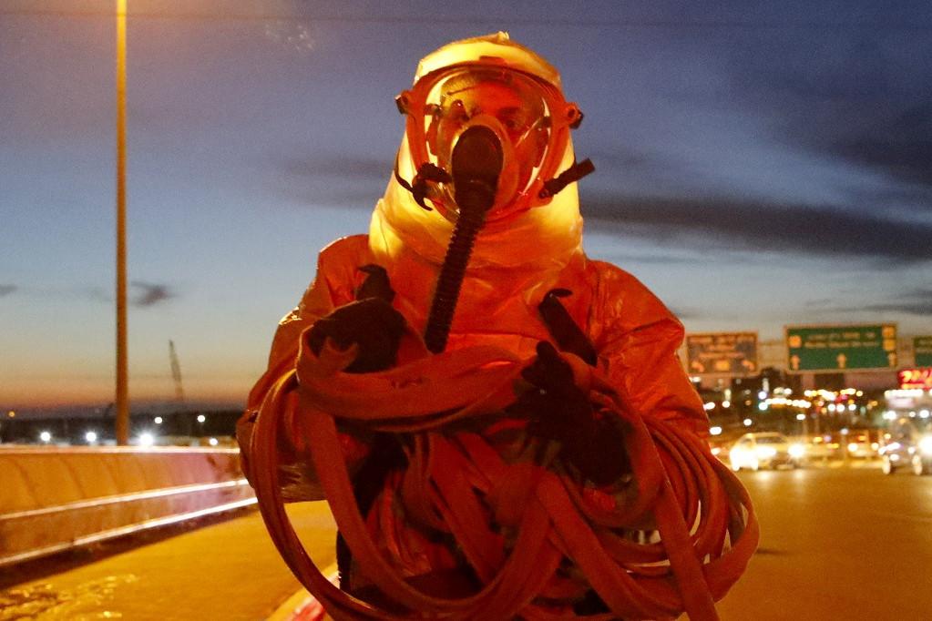 Fertőtlenítésre készülő tűzoltó védőruhában Izraelben
