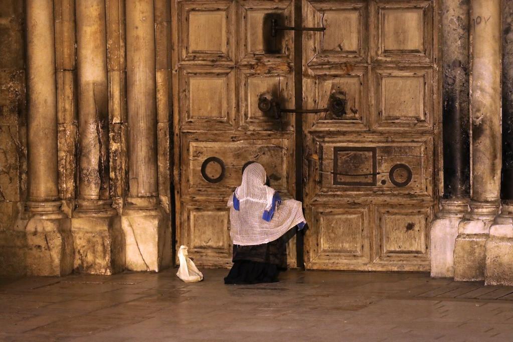 Egy hívő imádkozik a jeruzsálemi Szent Sír-templom zárt kapui előtt