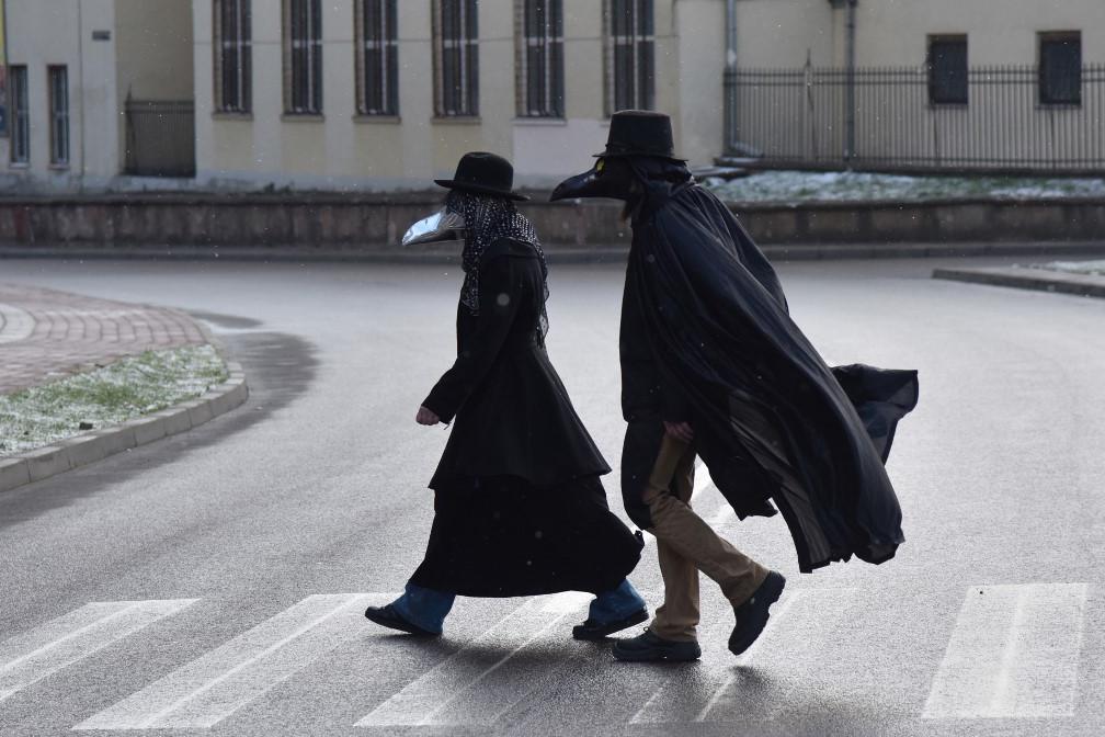 Járókelők pestisdoktor-maszkban Lvivben, Ukrajnában