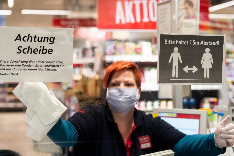 Egy német szupermarket dolgozója takarítja a bolt ablakát Drezdában
