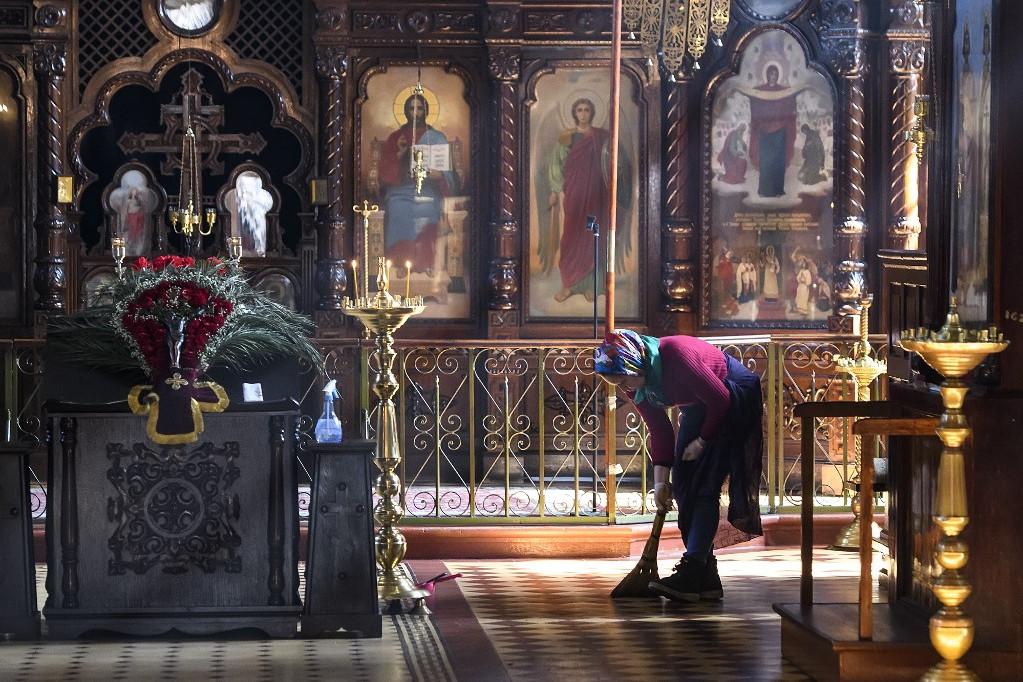 Idős hölgy takarítja egy templom padlóját Kijevben 2019. március 25-én
