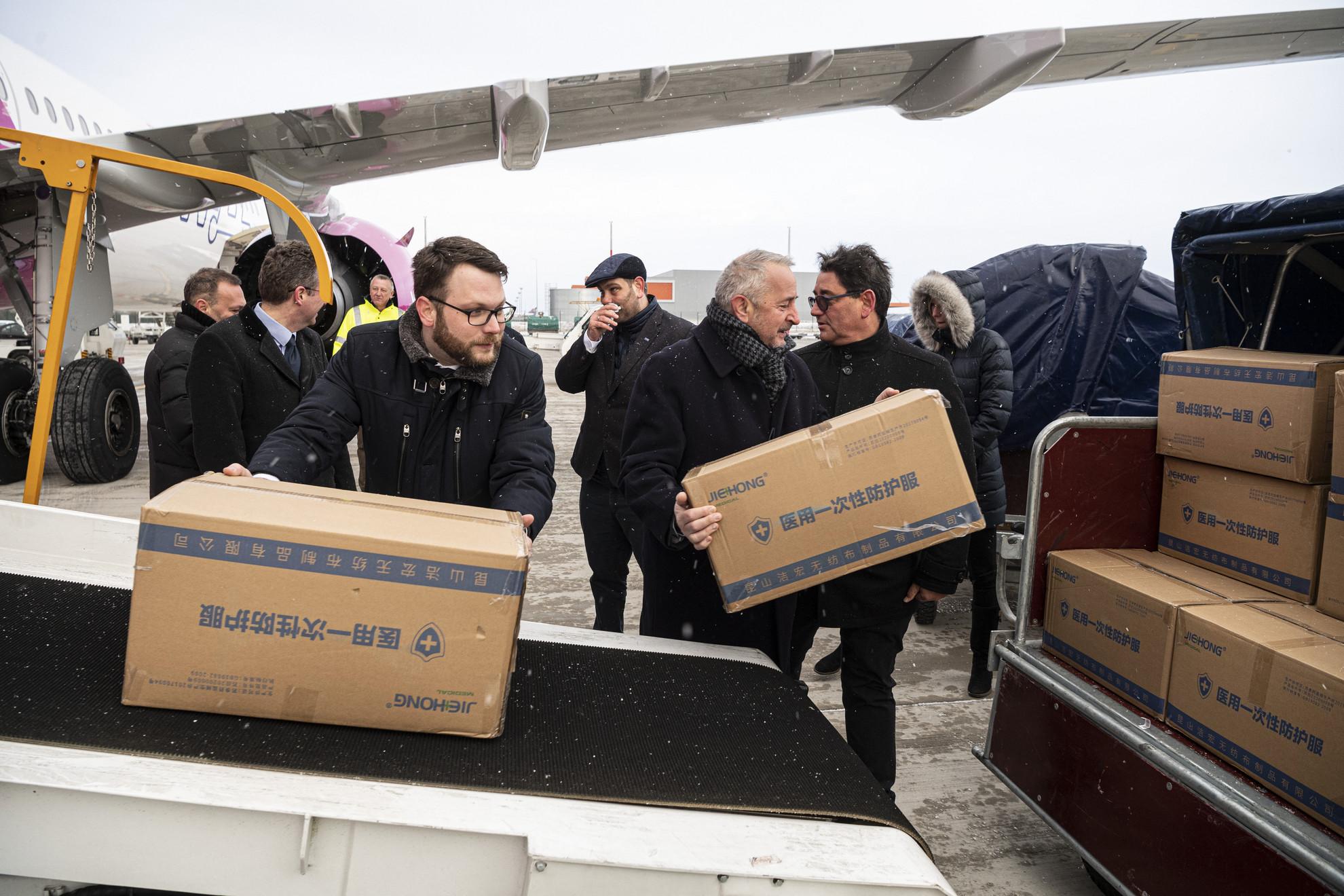 Schanda Tamás, az Innovációs és Technológiai Minisztérium (ITM) parlamenti és stratégiai államtitkára, Gondos Miklós, az Állami Egészségügyi Ellátó Központ főigazgatója és Merkely Béla, a Semmelweis Egyetem rektora (b-j) segít a Wizz Air Sanghajból érkezett repülőgép szállítmányának kipakolásában a Liszt Ferenc-repülőtéren 2020. március 23-án