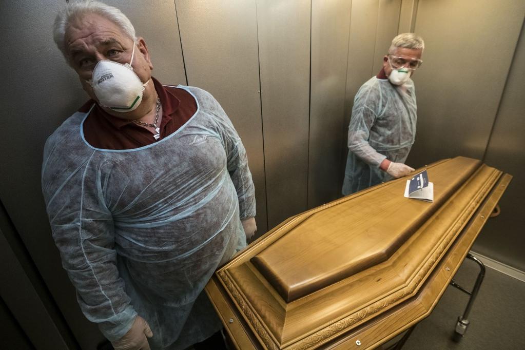 Egy francia temetkezési vállalat dolgozói állnak a liftben egy koronavírusban elhunyt személy koporsója mellett