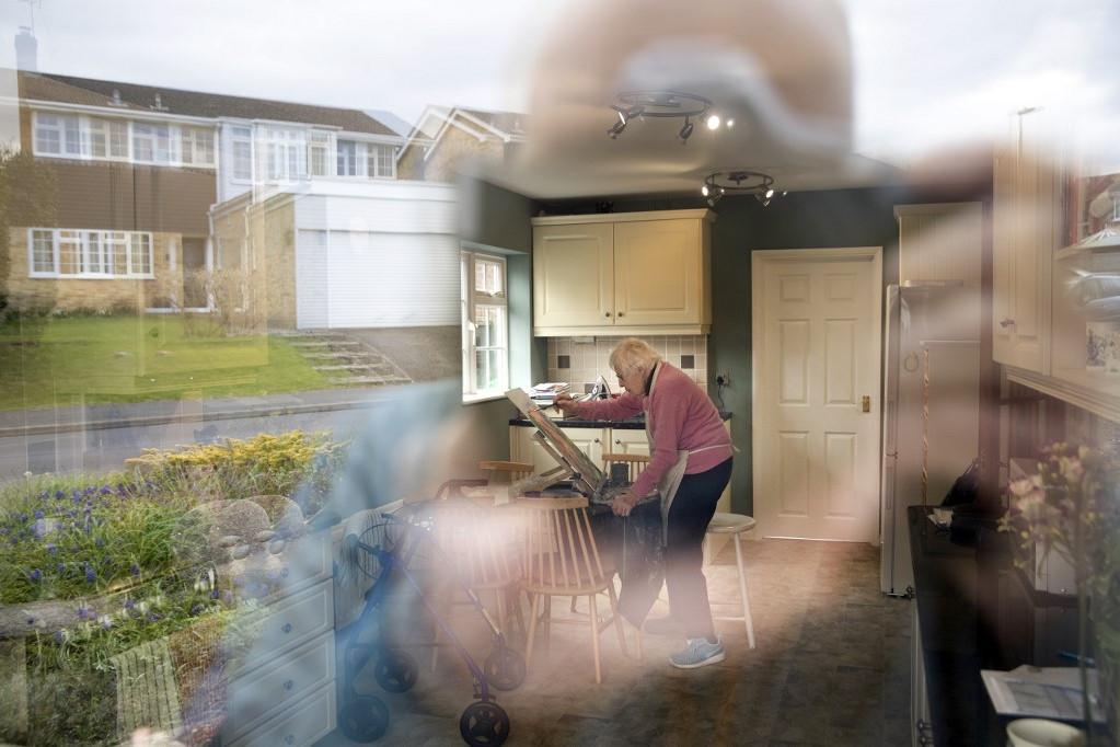 Idős hölgy fest az otthonában a koronavírus miatti korlátozások ideje alatt Nagy-Britanniában