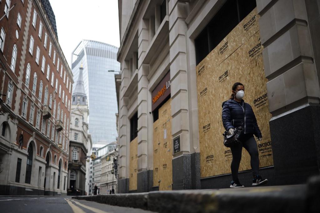 Bezárt boltok előtt sétáló nő a szinte kihalt Londonban