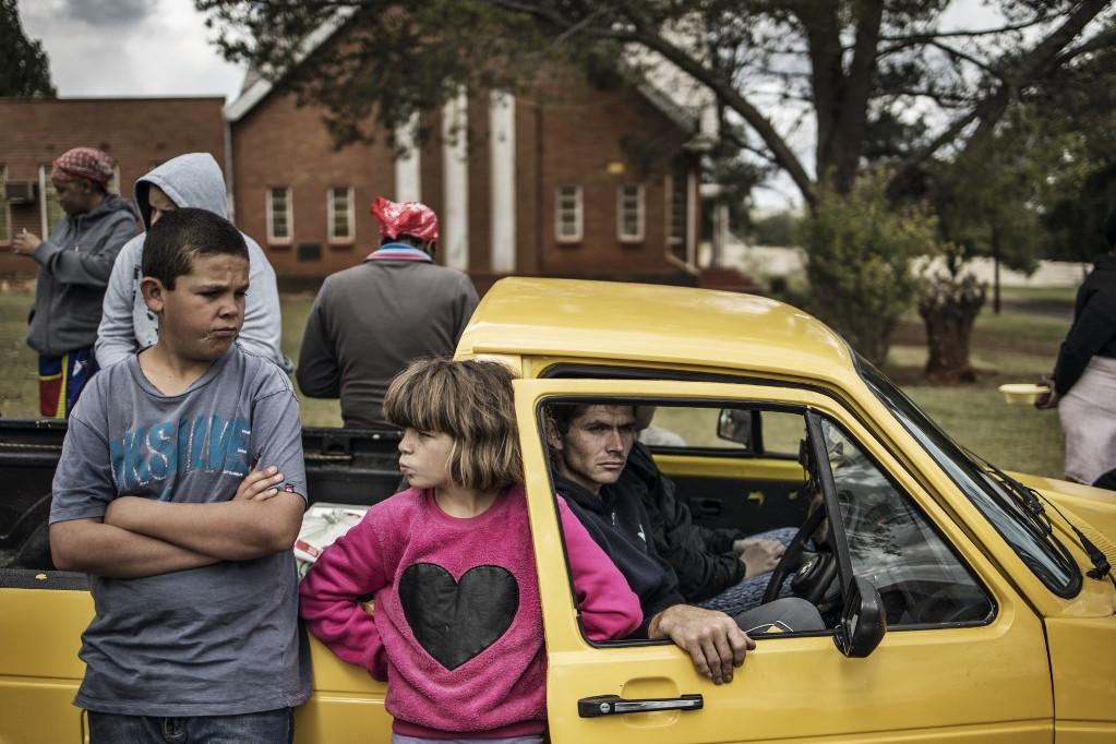 Ételosztásra váró család Johannesburgban, a Dél-afrikai Köztársaság legnagyobb városában