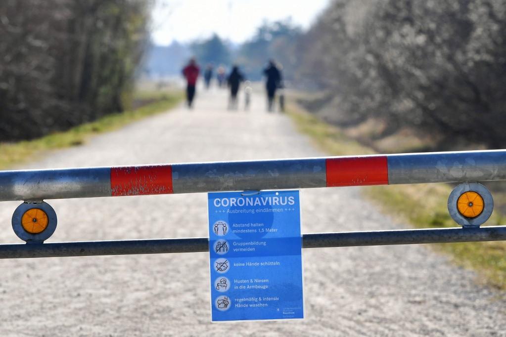 A koronavírusról szóló tájékoztató egy müncheni park sorompóján