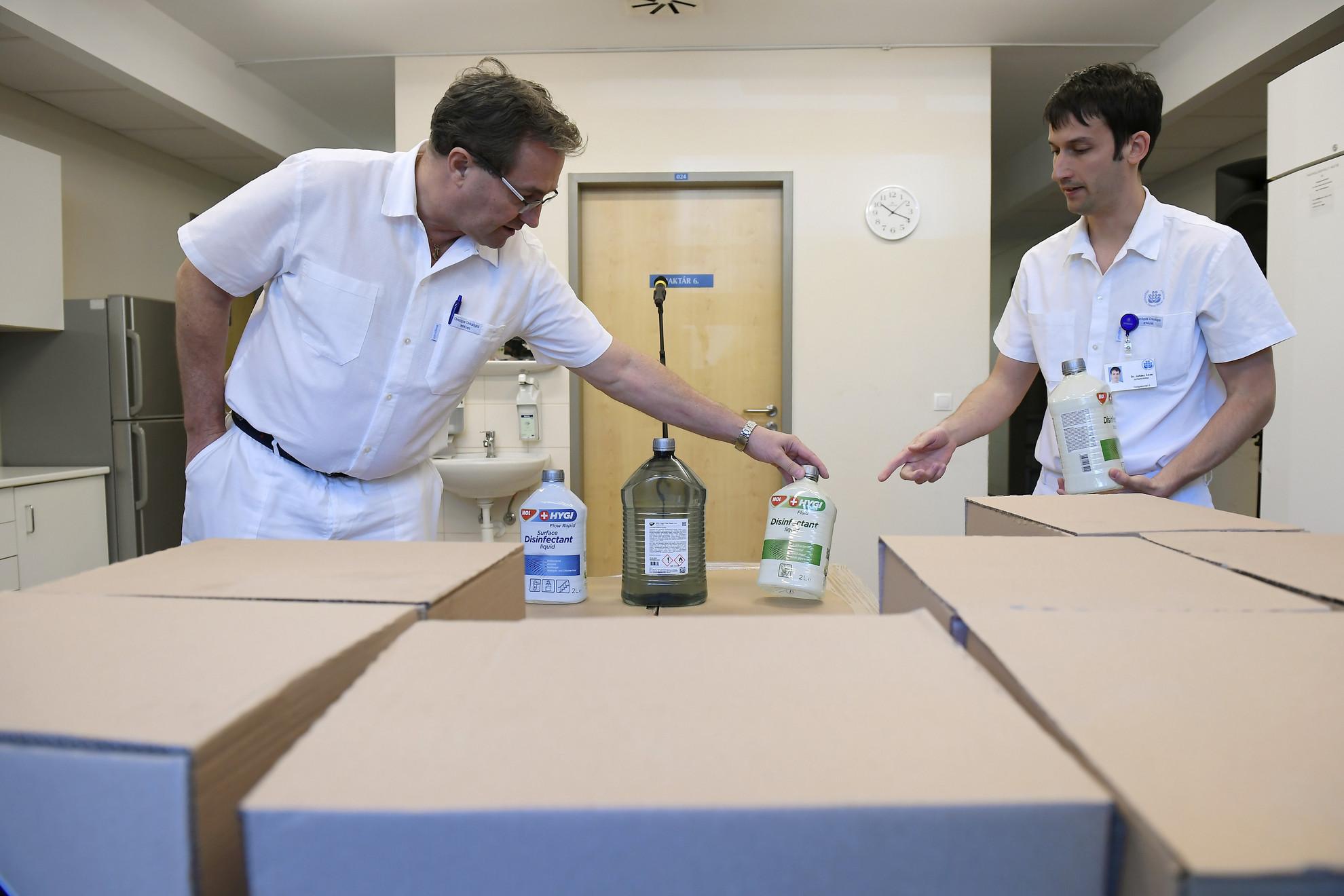 Polgár Csaba, az Országos Onkológiai Intézet főigazgató főorvosa (b) és Juhász Ákos, az intézet főgyógyszerésze átveszi a Mol kéz- és felületfertőtlenítő folyadék adományát a fővárosi intézet gyógyszerraktárában 2020. április 22-én