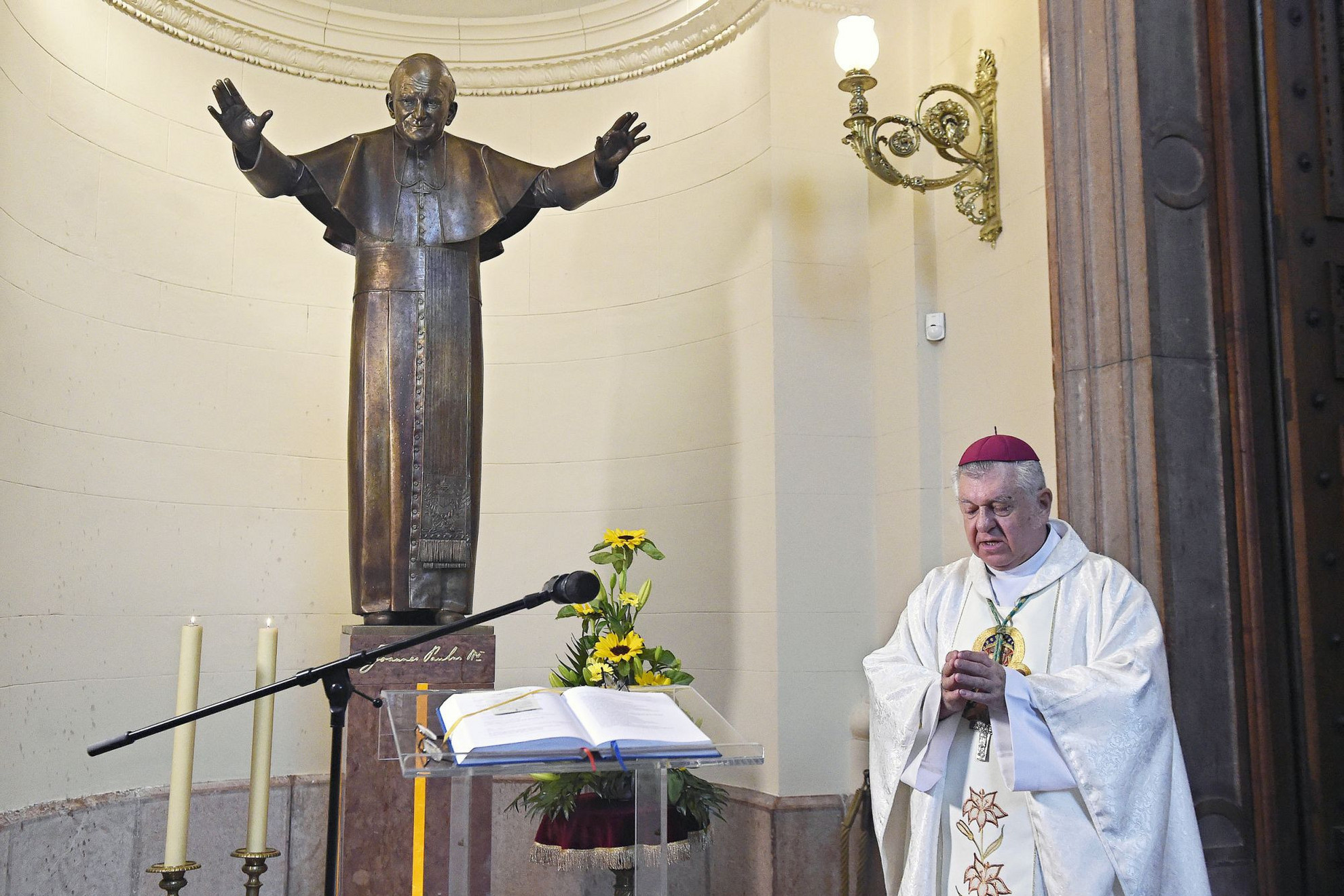 Megáldotta tegnap Szent II. János Pál pápa életnagyságú szobrát Snell György esztergom–budapesti segédpüspök, a Szent István-bazilika plébánosa (képünkön). A néhai pápa születésének századik évfordulója alkalmából felállított szobor Kotormán László és Kotormán Norbert szobrászművészek alkotása, és a főtemplom papi bejárójánál állították fel. A mű Snell György személyes ajándéka, felállításának gondolata néhány évvel ezelőtt, a volt Szent Jobb-kápolna átalakítása közben merült fel benne. Az elhelyezés koncepcióját Bukta Norbert festőművész és Galina Zoltán építész dolgozta ki. (UT)