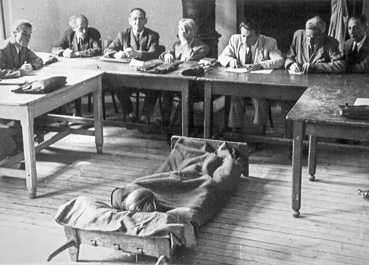 Kihelyezett tárgyalás a Gyűjtőfogházban az 1950-es években. A betegség nem akadály… A fényképezőgép sem, csak a bírák egyikének…