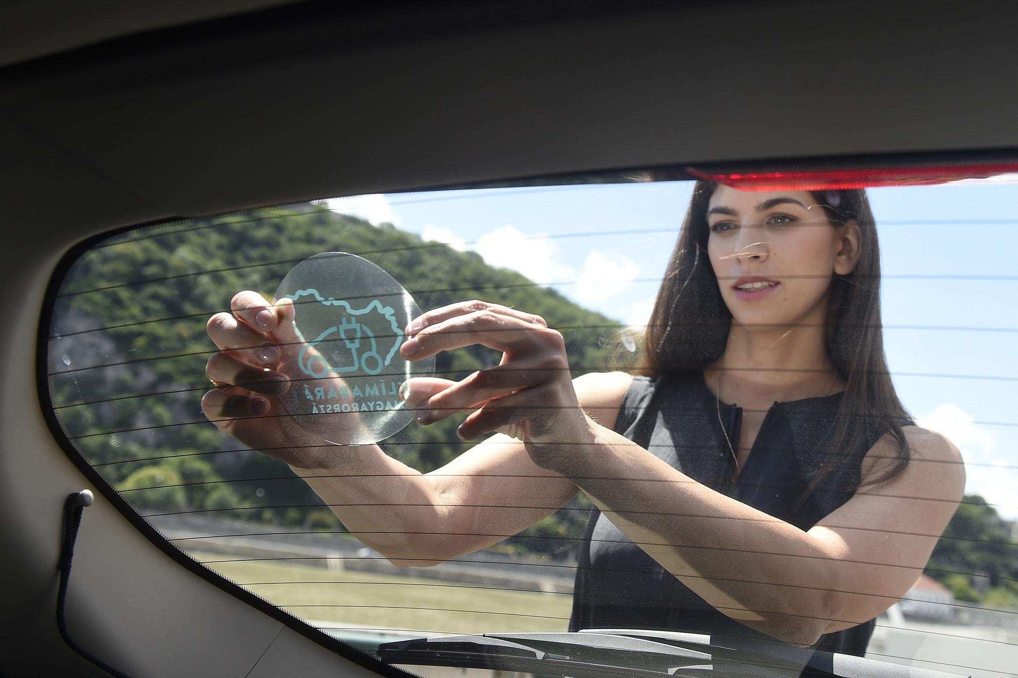 Szentkirályi Alexandra kormányszóvivő felragasztja egy autóra a kormány elektromobilitási támogatásával vásárolt járművekre felhelyezendő matricát az e-járművek vásárlását támogató pályázatról tartott sajtótájékoztatón a budapesti Belgrád rakparton 2020. július 6-án