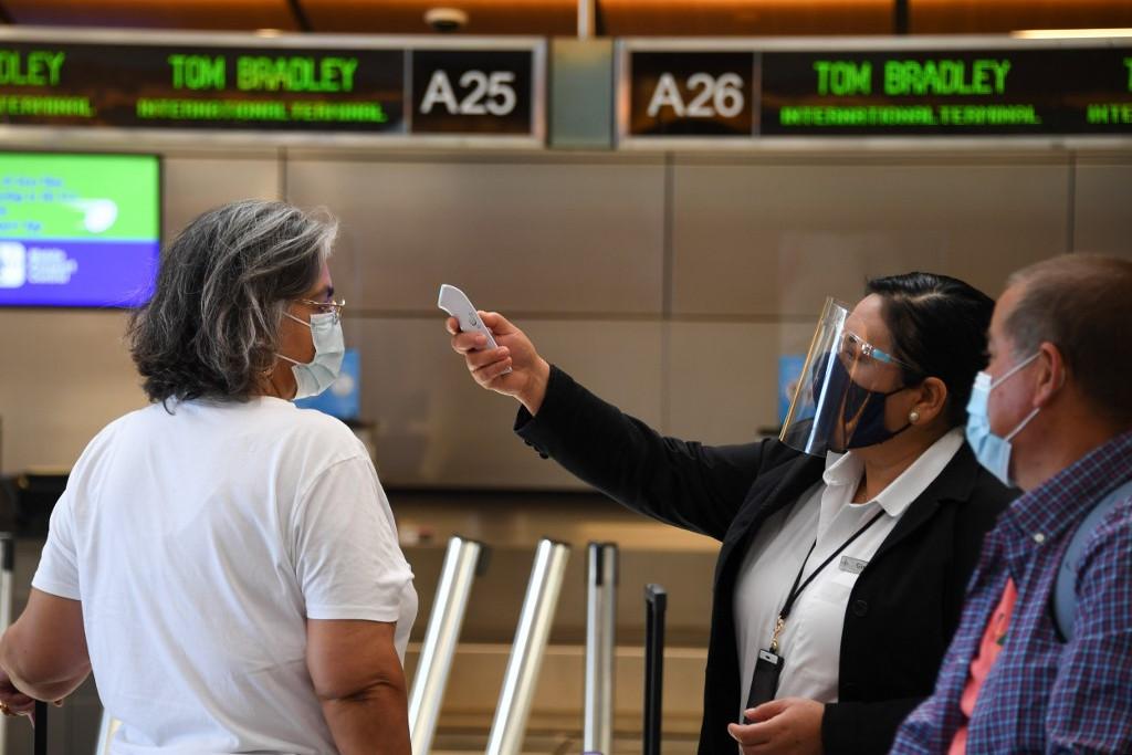 Egy reptéri dolgozó ellenőrzi az utasok testhőmérsékletét a Los Angeles-i nemzetközi repülőtéren