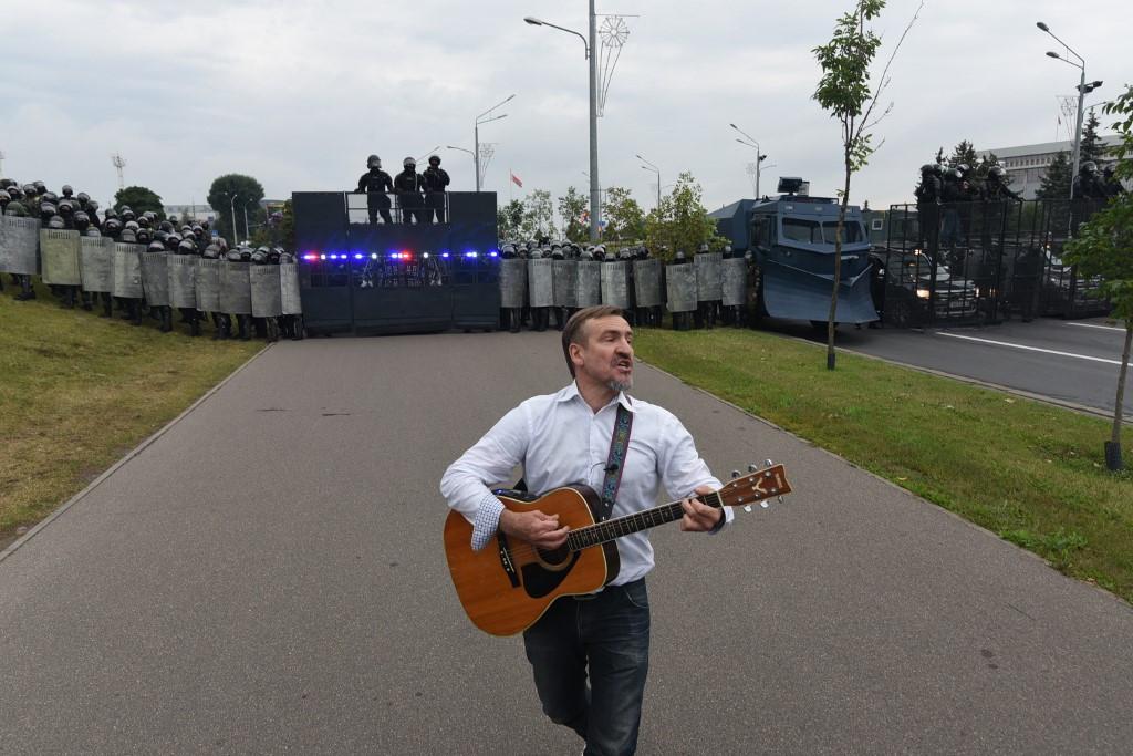 Tüntető gitárral a pajzzsal felszerelkezett rendőri erők sorfala előtt