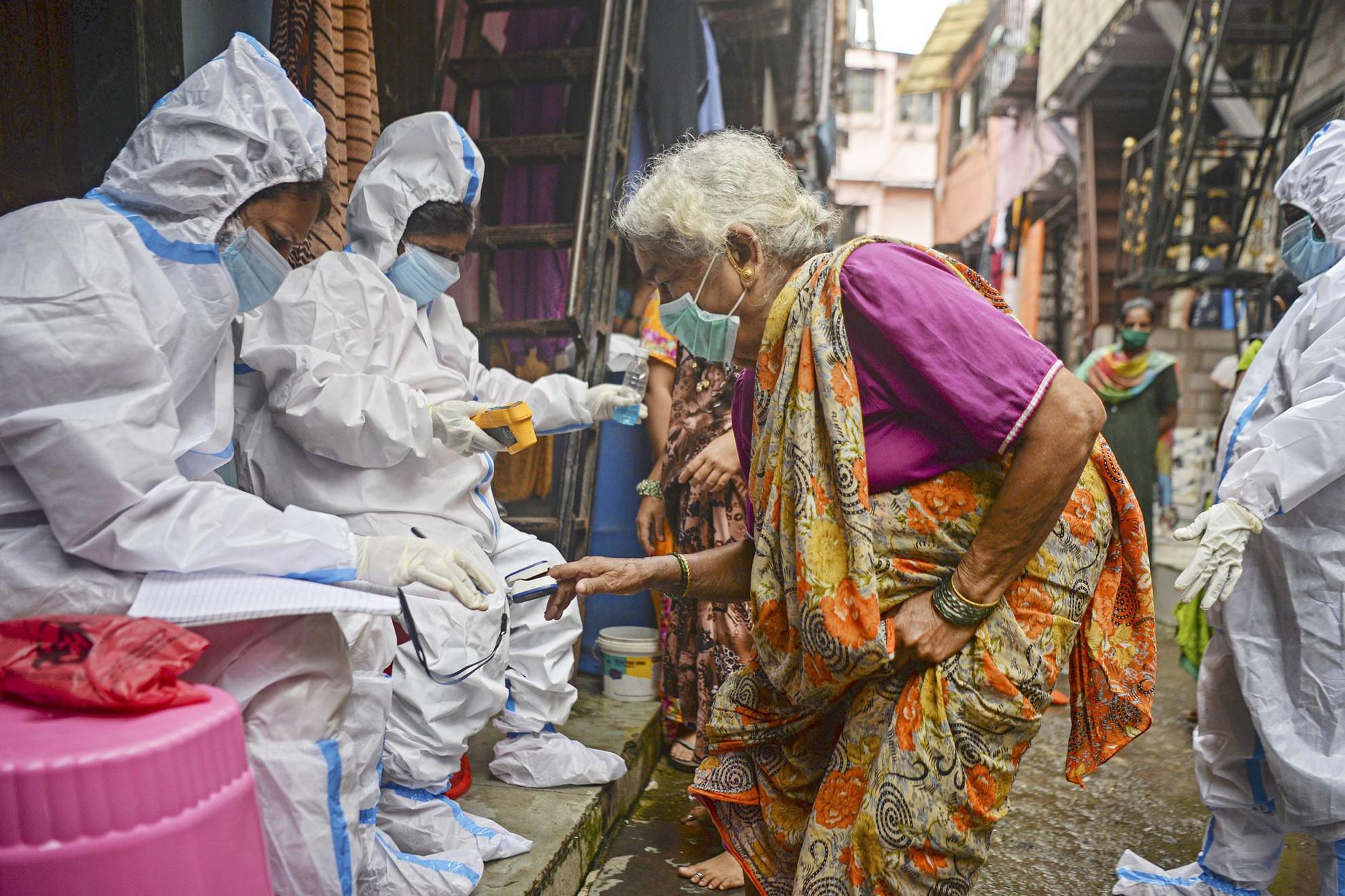 Egészségügyi dolgozók hőmérsékletméréseket végeznek az indiai Mumbaiban