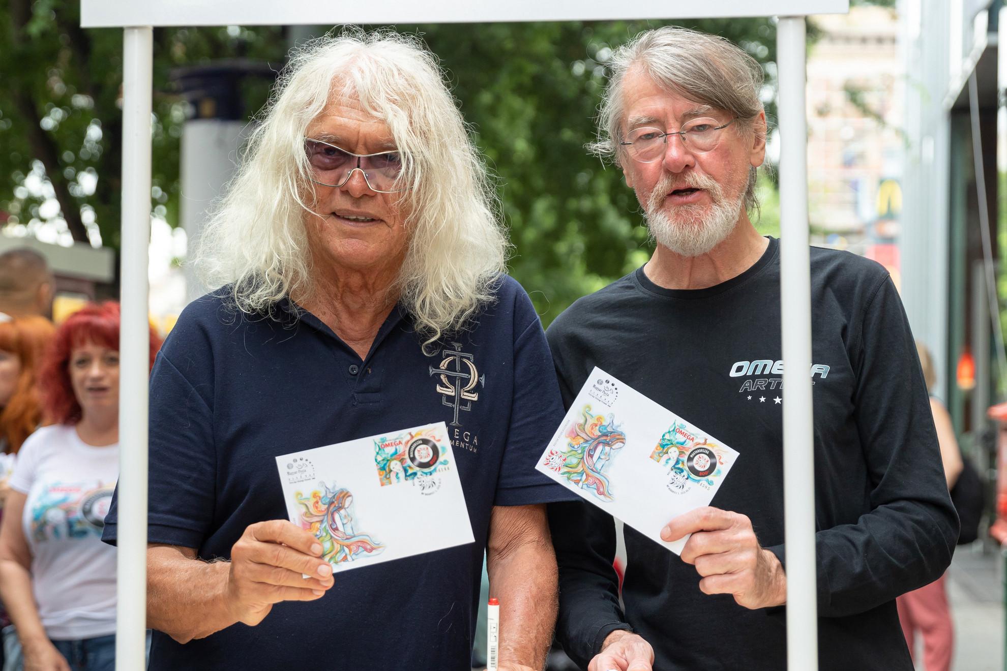 Az Omega együttes tagjai, Kóbor János énekes (b) és Debreczeni Ferenc dobos mutatja a Magyar Posta Magyar rockklasszikusok című bélyeg témasorozatának első darabját a budapesti 62-es postahivatal előtt a Nyugati téren