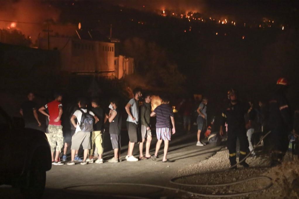 Migránsok gyülekeznek a kiürített tábor mellett