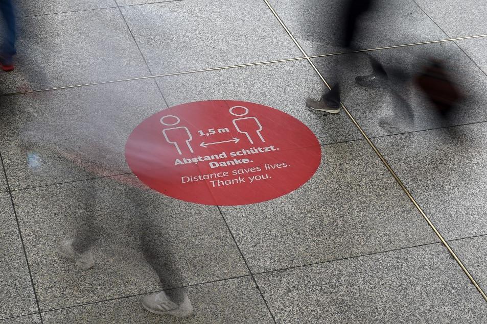 Másfél méteres távolság megtartására figyelmeztető jel Münchenben