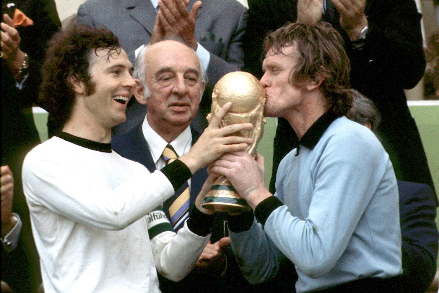 Beckenbauer a válogatott csapatkapitányaként is csúcsra ért, itt épp a Nationalelf kapusával, Sepp Maierrel ünnepli a világbajnoki győzelmet, mögött Hermann Gössmann, a Német Labdarúgó Szövetség elnöke