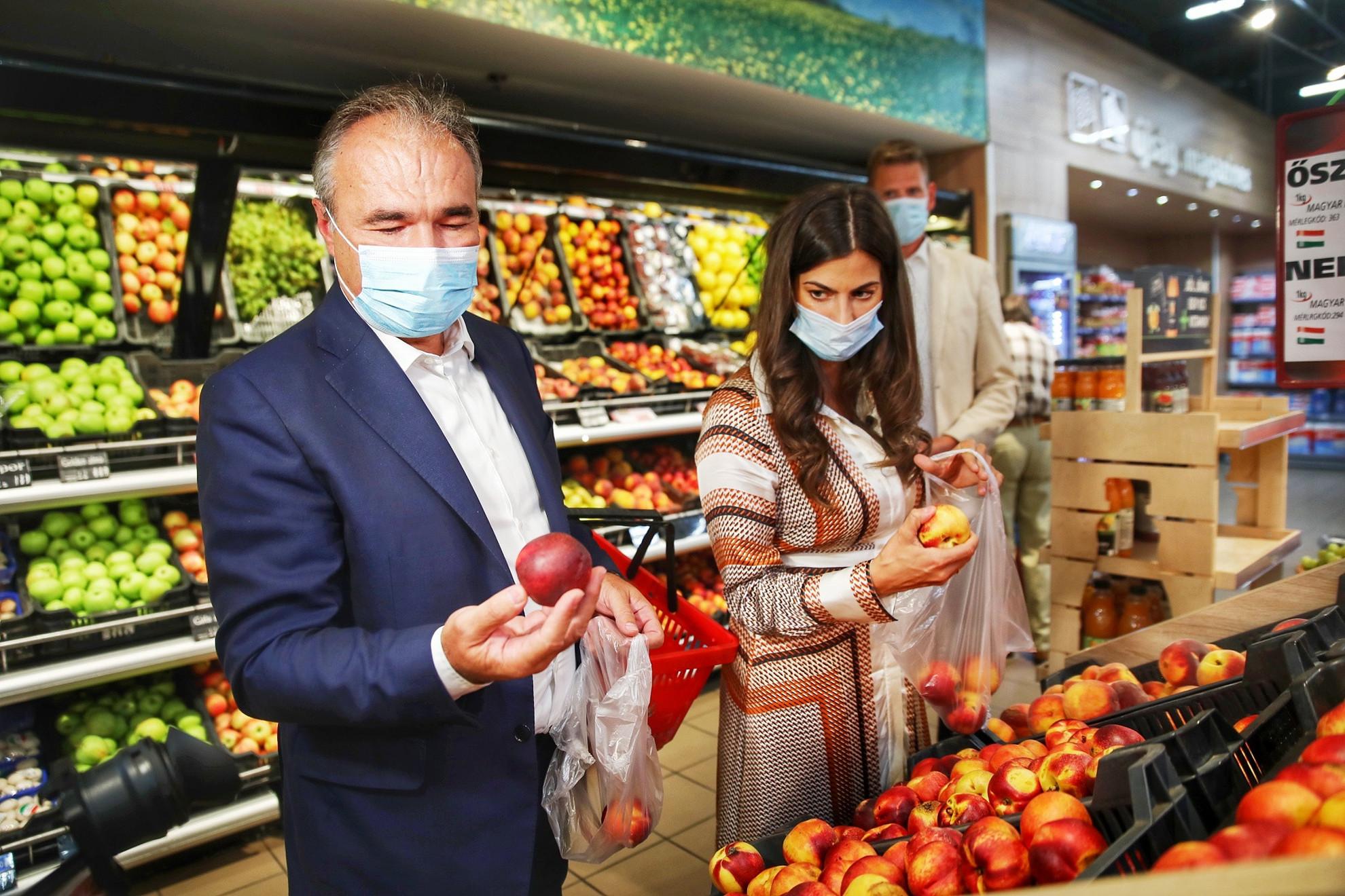 Nagy István agrárminiszter és Szentkirályi Alexandra kormányszóvivő hazai gyümölcsöket néz a Corvin áruházi CBA Prímában, Budapesten