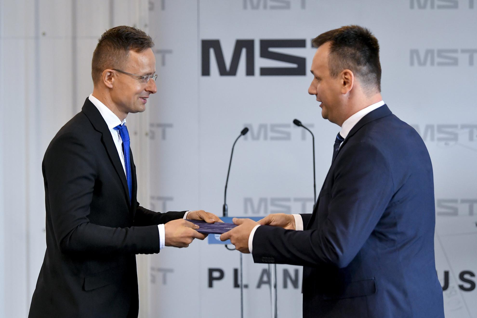 Szijjártó Péter (b) átadja a 282 millió forintos versenyképesség-növelő támogatásról szóló szerződést Bocskai Istvánnak, az MST-Engineering Kft. minőségi és értékesítési vezetőjének a cég debreceni üzemcsarnokában