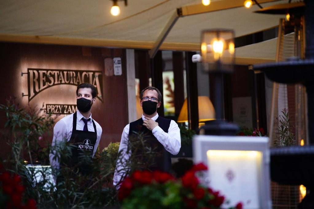 Védőmaszkos pincérek egy étterem előtt Varsó óvárosában