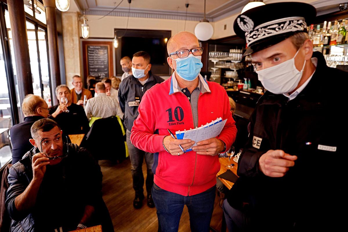 Rendőr ellenőrzi egy párizsi kávéházban a tulajdonos társaságában a szabályok betartását