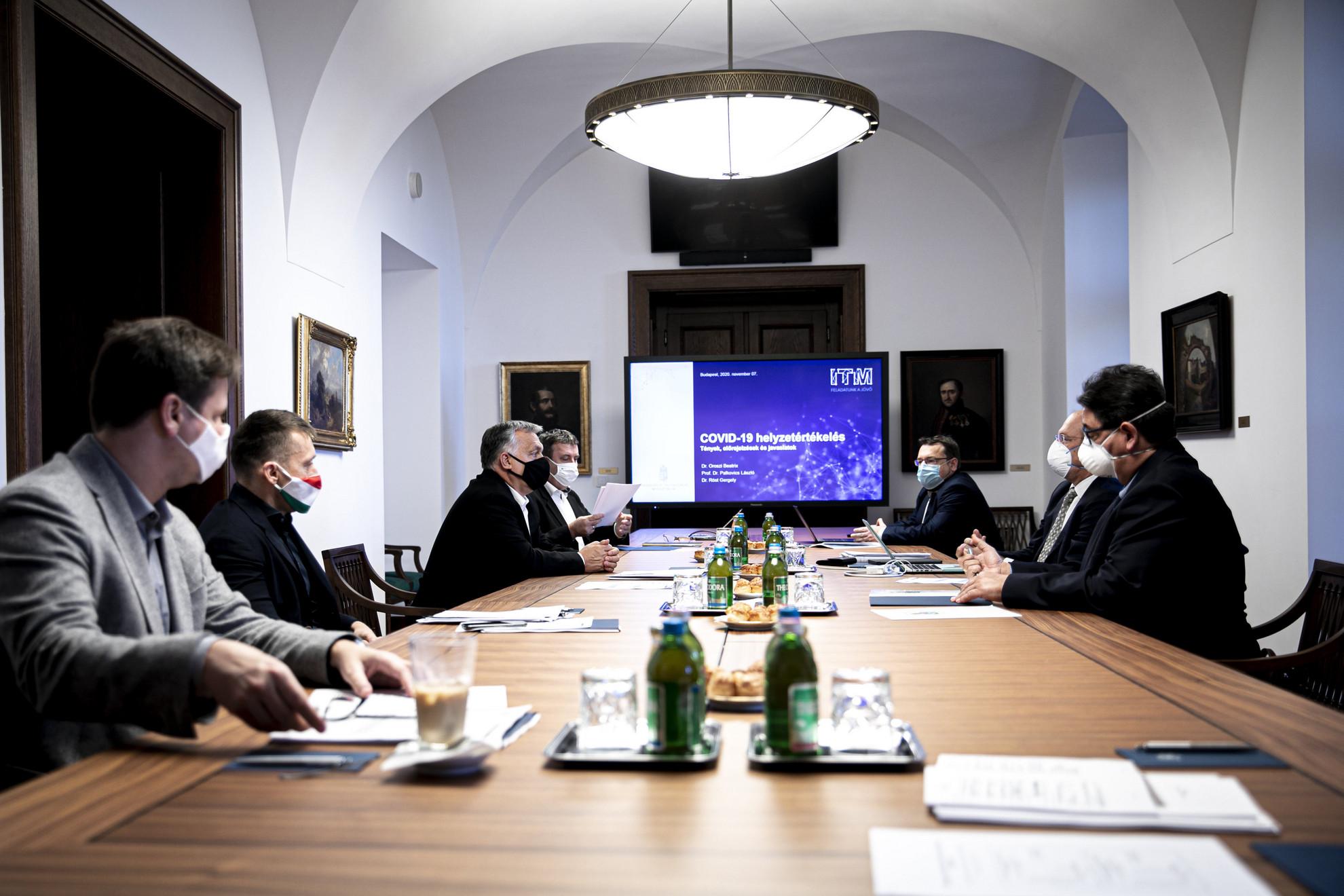 Orbán Viktor miniszterelnök (b3) tudományos szakemberekkel tanácskozik a Karmelita kolostorban 2020. november 7-én. Mellette Gulyás Gergely, a Miniszterelnökséget vezető miniszter (b), Rogán Antal, a Miniszterelnöki Kabinetirodát vezető miniszter (b2), Palkovics László innovációs és technológiai miniszter (b4), szemben Merkely Béla, a Semmelweis Egyetem rektora (j), Szócska Miklós, a Semmelweis Egyetem egészségügyi közszolgálati karának dékánja (j2) és Röst Gergely, a Szegedi Tudományegyetem járványtannal foglalkozó matematikusa (j3