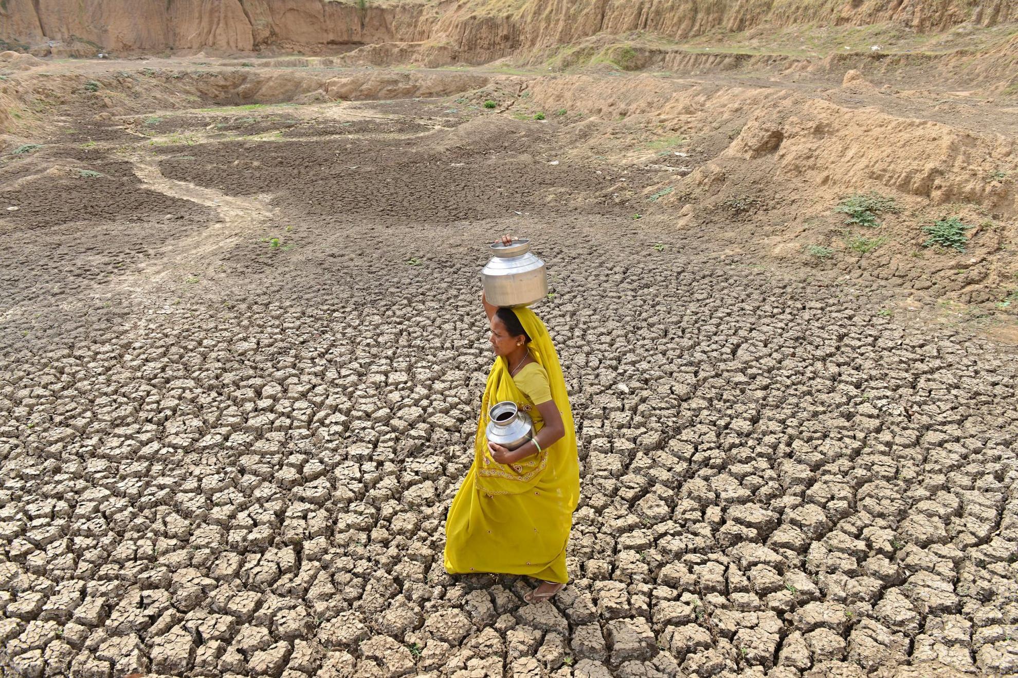 Egy indiai nő vízért megy egy kiszáradt tó medrén át Gujarat államban