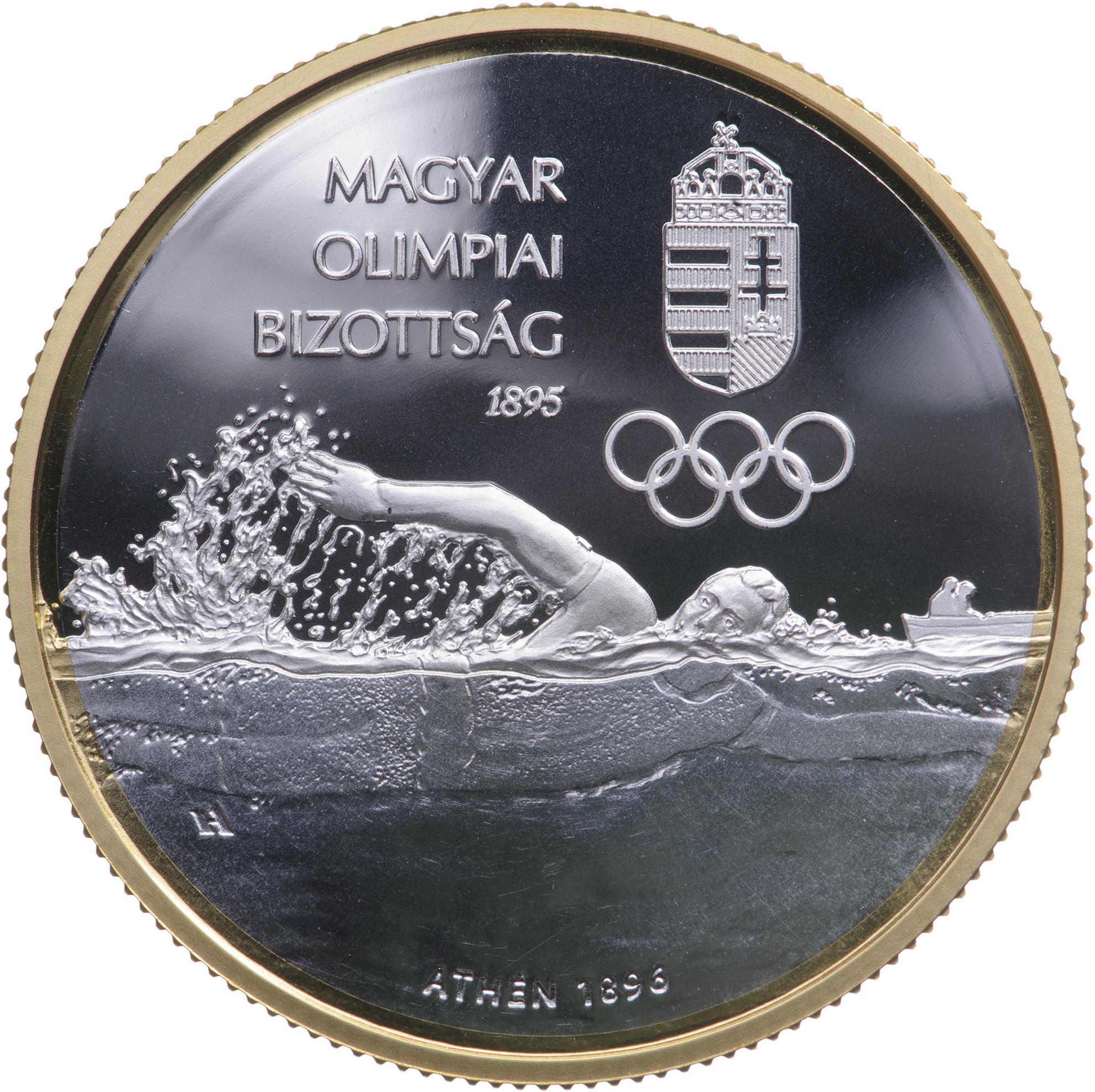Az emlékérmét tervező Horváth Andrea iparművész mesterjegye bal oldalon az úszó alakja alatt jelenik meg a tenger ábrázolásába rejtve