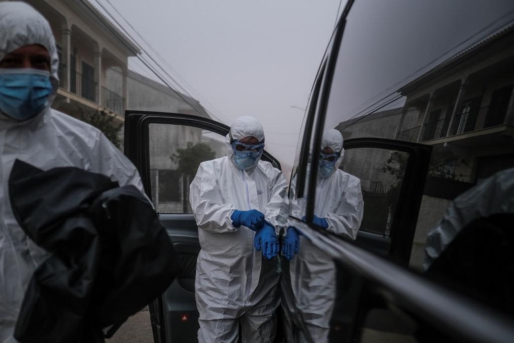 Halottszállítók érkeznek egy koronavírusban elhunyt ember lakásához Portugáliában január 29-én