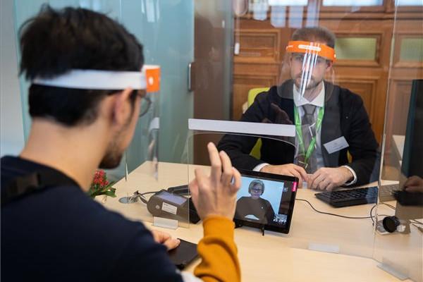 Ügyintéző arcpajzsban dolgozik a videóalapú Kontakt jelnyelvi szolgáltatás segítségével a Nyugati téri kormányablakban