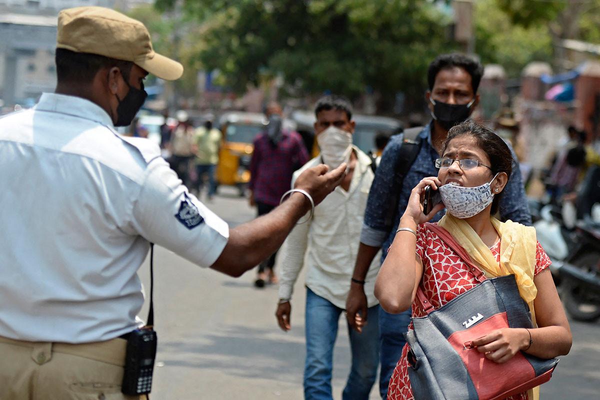 A helyes maszkviselésre figyelmeztetik a járókelőket Haidarábád nagyvárosban.