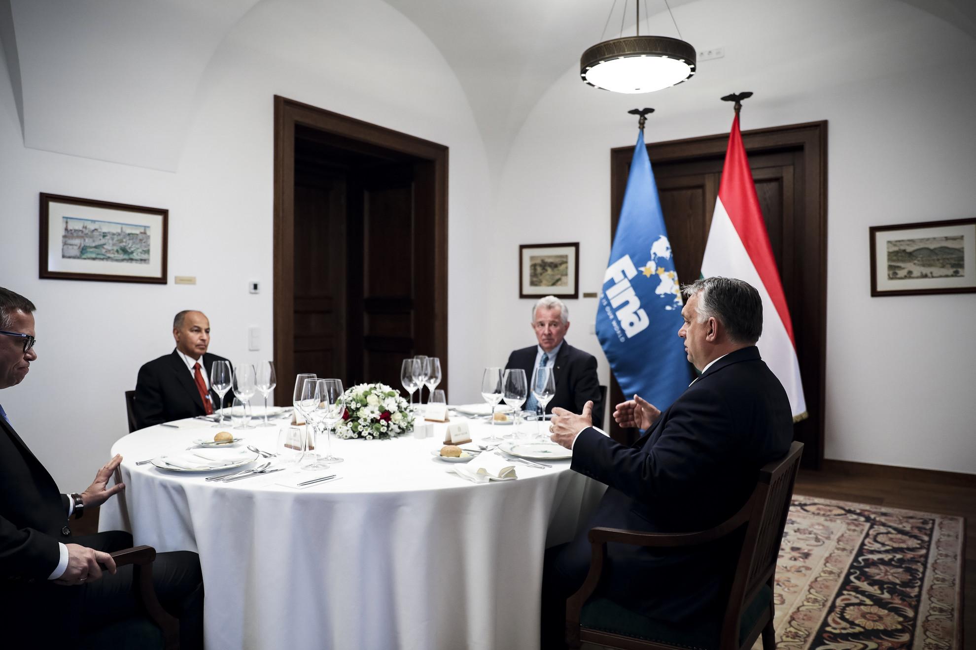 Orbán Viktor kormányfő (j) fogadja Huszain al-Muszallamot, a Nemzetközi Úszószövetség (FINA) első alelnökét, a szervezet elnökjelöltjét (b2) a Karmelita kolostorban 2021. május 17-én. Mellettük Fürjes Balázs, a Miniszterelnökség Budapest és a fővárosi agglomeráció fejlesztéséért felelős államtitkára (b) és Schmitt Pál, a Magyar Olimpiai Bizottság (MOB) tiszteletbeli elnöke, korábbi köztársasági elnök (j2).