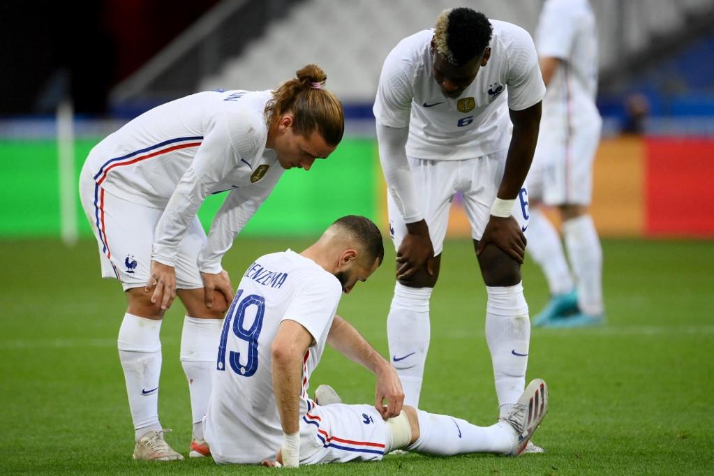 Antoine Griezmann (b) és Paul Pogba (j) figyelik a megsérült Karim Benzemát