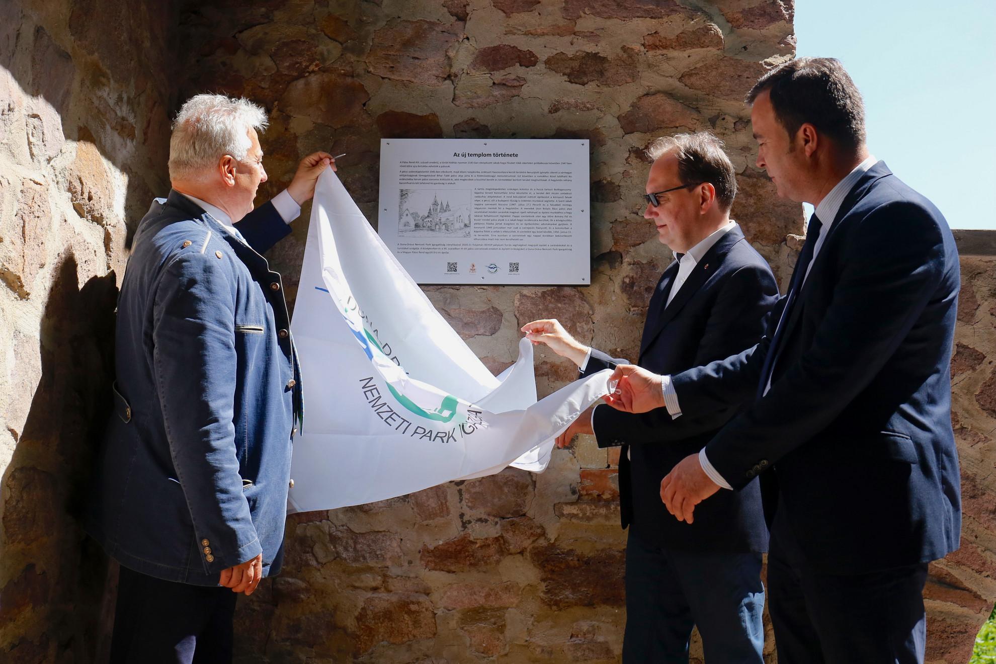 Semjén Zsolt miniszterelnök-helyettes,  Hoppál Péter, a Fidesz országgyűlési képviselője és Rácz András, az Agrárminisztérium környezetügyért felelős államtitkára (b-j) leleplezi az emléktáblát a közelmúltban felújított Új templom turistapihenő átadásán a mecseki Jakab-hegyen