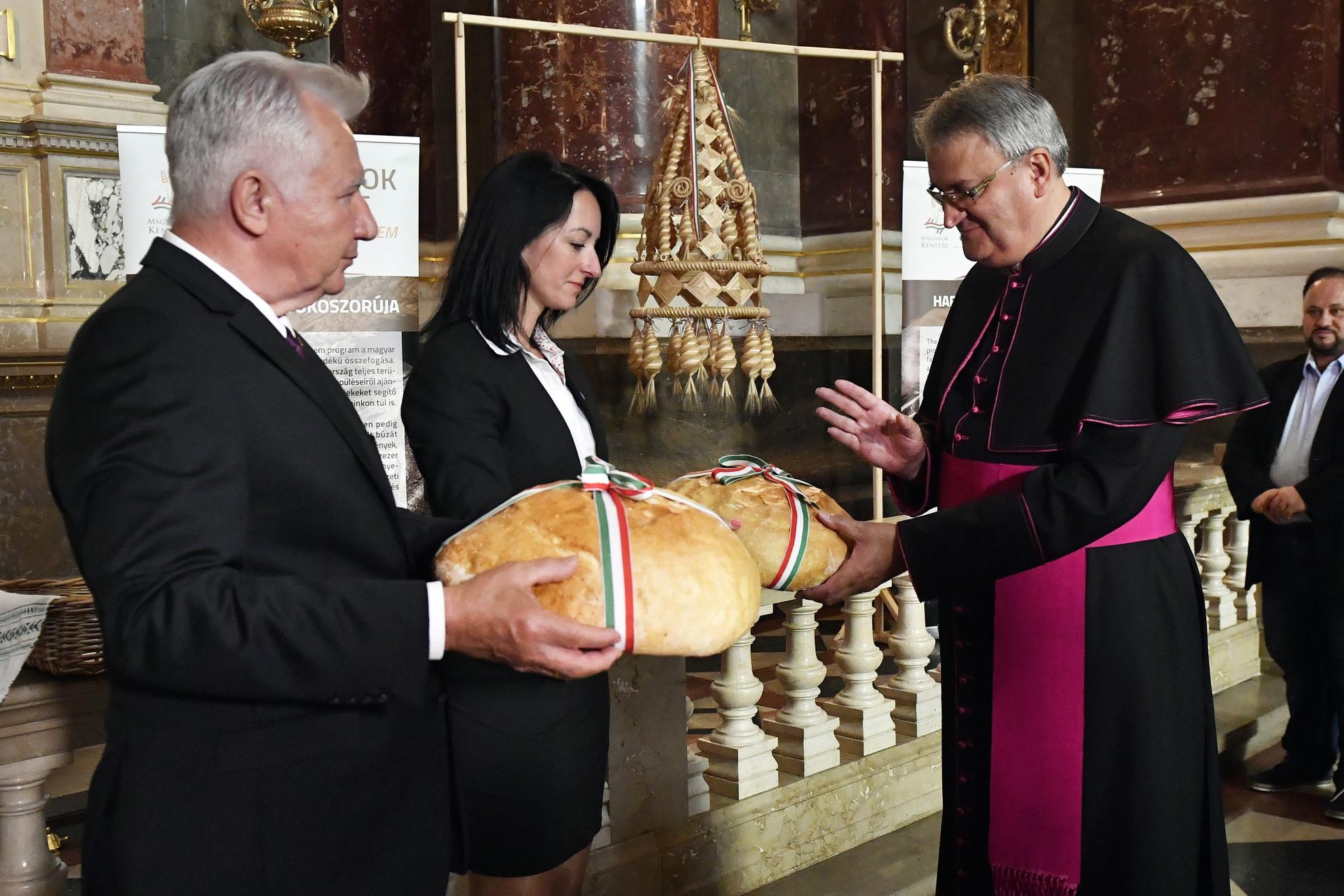 Horváth Zoltán plébános megáldja az új kenyeret a Magyarok Kenyere - 15 millió búzaszem program keretében elkészült, a magyarság összetartozását és a gazdaösszefogást szimbolizáló Kárpát-medence Aratókoszorúja átadásán a Szent István-bazilikában