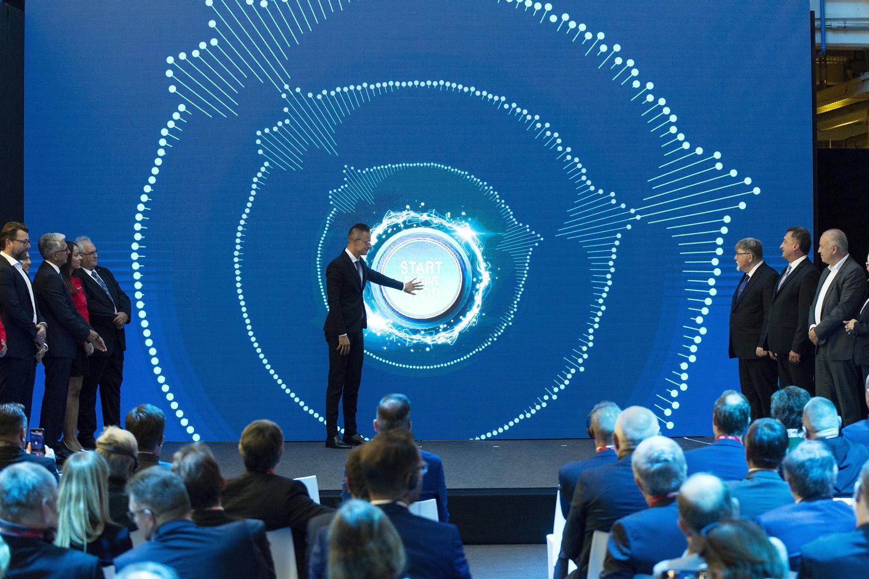 Szijjártó Péter az Audi Hungária Zrt. további fejlesztéseit jelképező indítógombnál a cég jubileumi rendezvényén